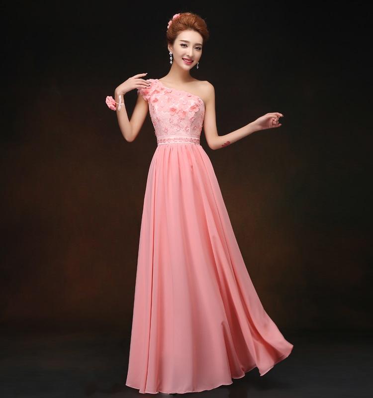 ชุดเดรสยาว ไหล่เฉียง สีชมพู ตัวเสื้อผ้าลูกไม้ แต่งด้วยผ้าถักรูปดอกไม้ ที่เสื้อและเอว